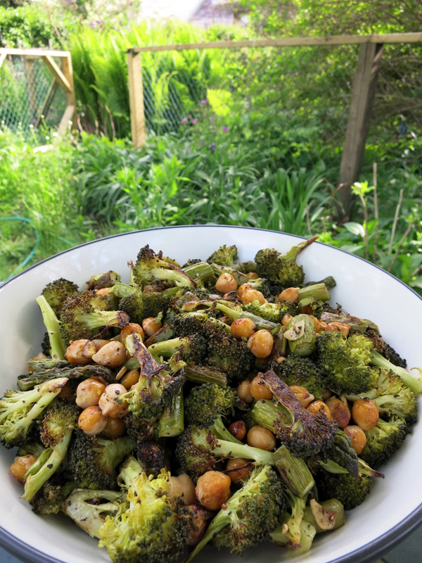 Roasted black pepper broccoli in a bowl set by a garden