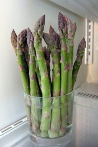 Asparagus standing upright in water in a fridge
