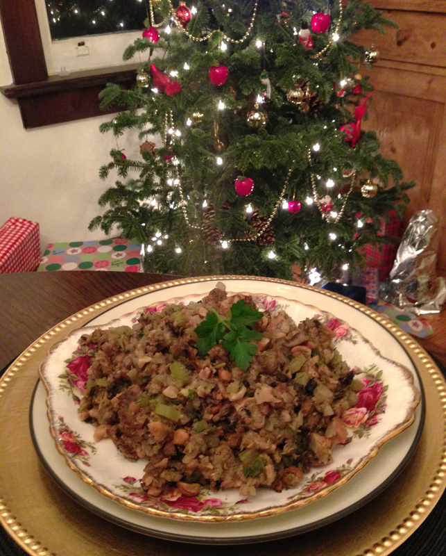 Mushroom and cashew stuffing in a bowl with a lit Christmas tree in the background