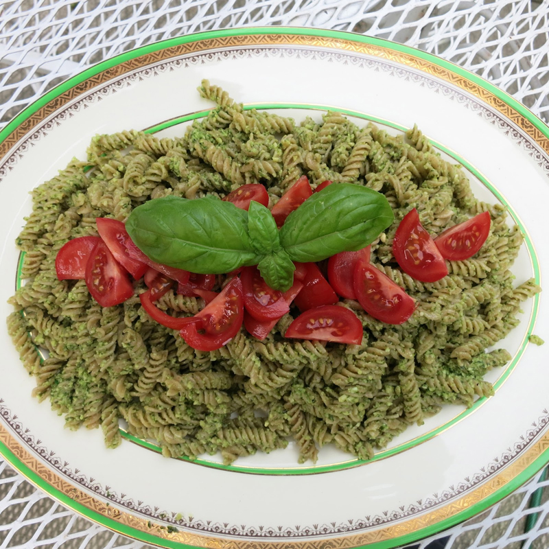 Basil and cashew pesto on pasta with tomatoes on top